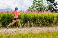 Jovem mulher que corre na estrada secundária nas montanhas, dia de verão Foto de Stock