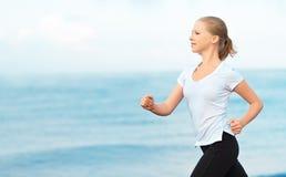 Jovem mulher que corre na praia na costa do mar fotografia de stock