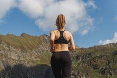 Jovem mulher que corre nas montanhas durante um dia ensolarado imagem de stock royalty free