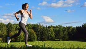 Jovem mulher que corre no parque durante o treinamento do esporte fotos de stock royalty free
