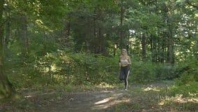Jovem mulher que corre no parque, manhã filme