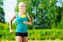 Jovem mulher que corre no parque verde Fotografia de Stock Royalty Free