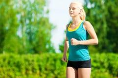 Jovem mulher que corre no parque verde Imagens de Stock Royalty Free