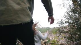 Jovem mulher que corre a uma plataforma de observação e para chamar um homem com ela video estoque