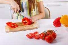 Jovem mulher que corta legumes frescos foto de stock