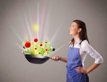 Jovem mulher que cozinha legumes frescos Imagens de Stock Royalty Free