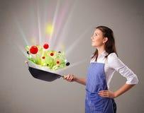 Jovem mulher que cozinha legumes frescos Imagens de Stock