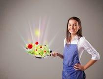 Jovem mulher que cozinha legumes frescos Foto de Stock Royalty Free