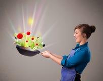 Jovem mulher que cozinha legumes frescos Fotos de Stock