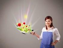 Jovem mulher que cozinha legumes frescos Fotografia de Stock