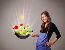 Jovem mulher que cozinha legumes frescos imagem de stock