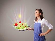 Jovem mulher que cozinha legumes frescos Foto de Stock
