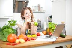 Jovem mulher que cozinha na cozinha Alimento saudável - Sal vegetal fotografia de stock royalty free
