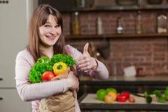 Jovem mulher que cozinha na cozinha em casa A menina na cozinha guarda um saco de papel com legumes frescos e verdes Fotografia de Stock