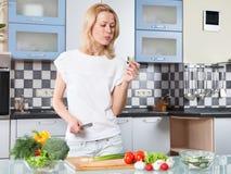 Jovem mulher que cozinha o alimento e a parte de testes saudáveis Imagem de Stock Royalty Free
