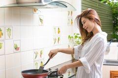 Jovem mulher que cozinha o alimento saud?vel em casa imagem de stock