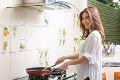 Jovem mulher que cozinha o alimento saud?vel em casa fotografia de stock royalty free