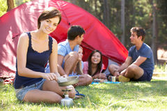 Jovem mulher que cozinha o café da manhã para amigos no feriado de acampamento Imagens de Stock Royalty Free