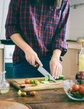 Jovem mulher que cozinha a cozinha simples da casa do alimento do vegetariano saudável Fotografia de Stock