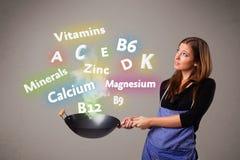 Jovem mulher que cozinha vitaminas e minerais Fotografia de Stock