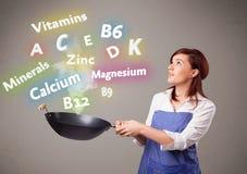 Jovem mulher que cozinha vitaminas e minerais Imagens de Stock