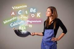 Jovem mulher que cozinha vitaminas e minerais Fotografia de Stock Royalty Free