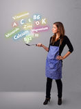 Jovem mulher que cozinha vitaminas e minerais Imagem de Stock