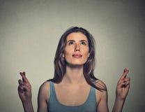 Jovem mulher que cruza seus dedos que olham acima Fotos de Stock Royalty Free