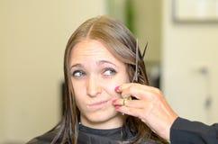 Jovem mulher que dá ao cabeleireiro um olhar duvidoso Fotos de Stock