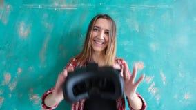 Jovem mulher que dá auriculares da realidade virtual filme