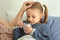 Jovem mulher que dá o comprimido para sua filha doente na cama foto de stock royalty free