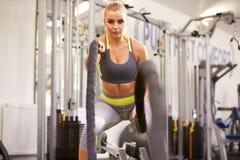 A jovem mulher que dá certo com batalha ropes em um gym Imagem de Stock