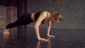 A jovem mulher que da aptidão fazer empurra levanta na esteira do exercício Fêmea nova saudável que dá certo em casa mulher moren filme