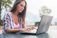 Jovem mulher que datilografa em um portátil que estuda ou que trabalha no parque Fotografia de Stock Royalty Free