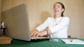 A jovem mulher que datilografa muito rapidamente em um portátil com uma expressão facial gosta louco Trabalho pesado do freelance video estoque