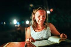 A jovem mulher que descansa em um café exterior olha o menu no mar em luzes bonitas do bokeh Fotografia de Stock Royalty Free