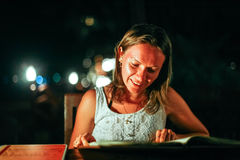 A jovem mulher que descansa em um café exterior olha o menu no mar em luzes bonitas do bokeh Fotos de Stock