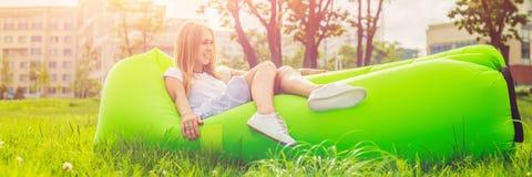 Jovem mulher que descansa em um sofá do ar no parque BANDEIRA, formato longo Fotografia de Stock