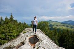 Jovem mulher que descansa em uma pedra grande no dia de verão nas montanhas Carpathian foto de stock royalty free