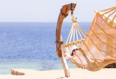 Jovem mulher que descansa na rede perto do mar Fotos de Stock