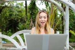 Jovem mulher que descansa no balanço e que usa o portátil, palmas no fundo fotos de stock royalty free