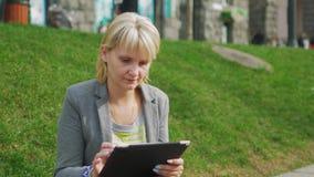 A jovem mulher que descansa no parque, aprecia uma tabuleta digital vídeos de arquivo