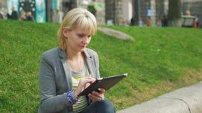A jovem mulher que descansa no parque, aprecia uma tabuleta digital video estoque