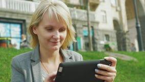 A jovem mulher que descansa no parque, aprecia uma tabuleta digital filme