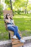Jovem mulher que descansa no parque no banco Relaxamento f?mea bonito em um banco de parque e utiliza??o de um smartphone toned fotografia de stock
