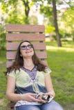 Jovem mulher que descansa no parque no banco Relaxamento f?mea bonito em um banco de parque e utiliza??o de um smartphone toned imagens de stock royalty free