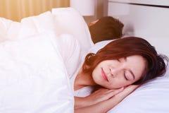 Jovem mulher que dorme com seu marido em uma cama em casa Imagem de Stock Royalty Free