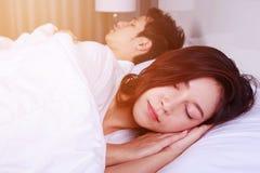 Jovem mulher que dorme com seu marido em uma cama em casa Fotografia de Stock