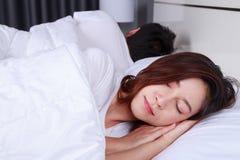 Jovem mulher que dorme com seu marido em uma cama em casa Fotos de Stock Royalty Free