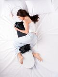 Jovem mulher que dorme e que abraça o snowboard Fotografia de Stock Royalty Free